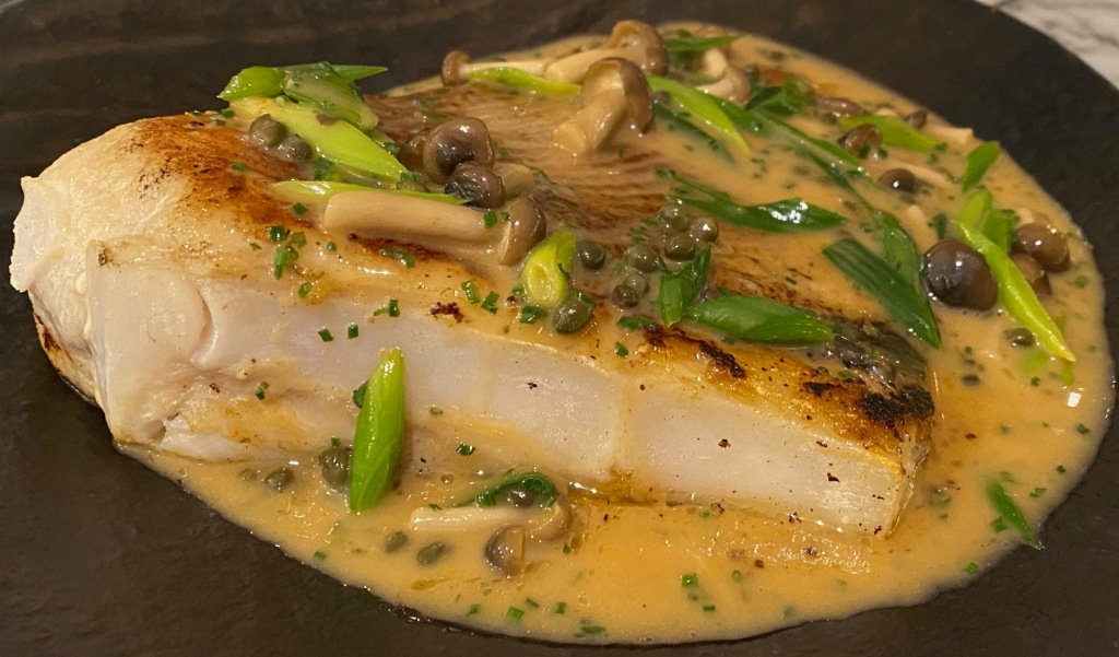 Fat skate wing burnished gold with creamy chicken sauce, mushrooms, and green chopped spring onion