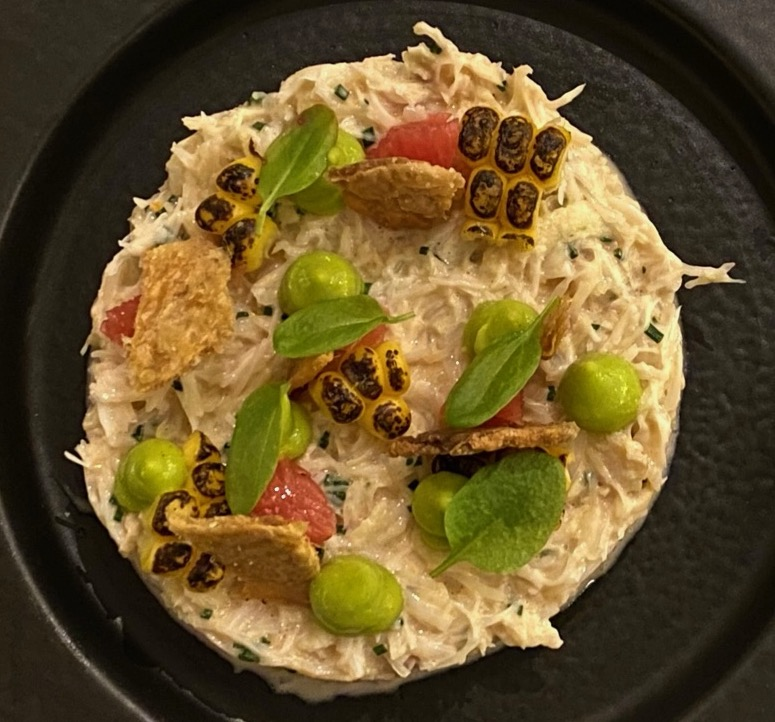 White crab meat in a ring dressed with avocado puree, burned sweetcorn, and grapefruit