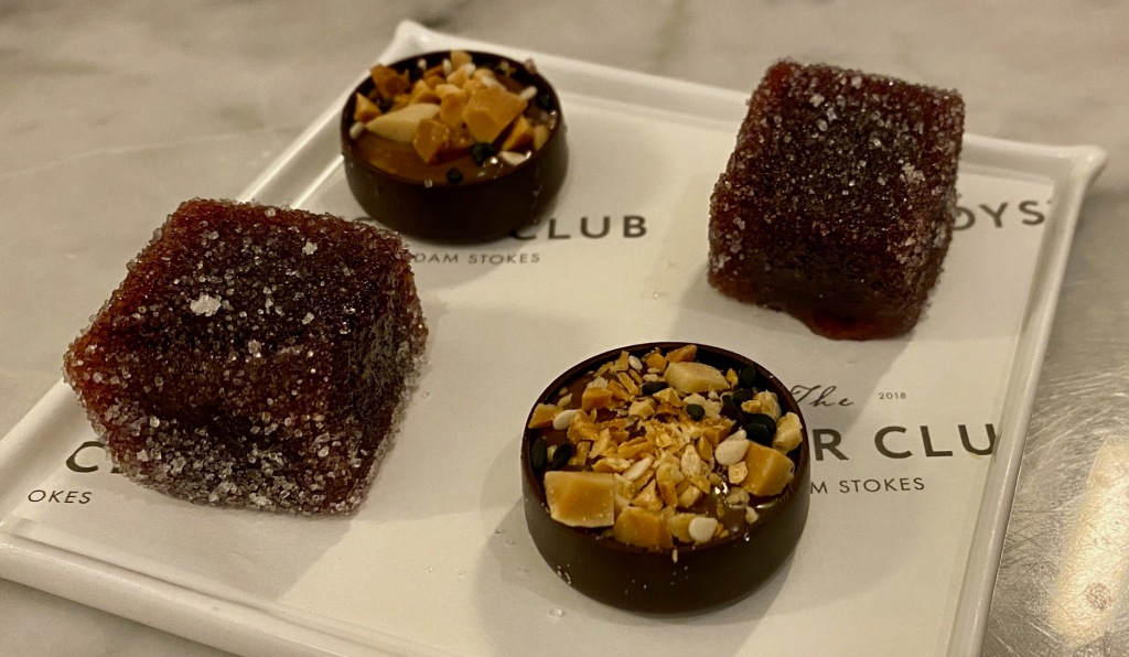 4 petit fours, 2 purple cubes of plum jelly, and two round chocolates topped with chopped nuts