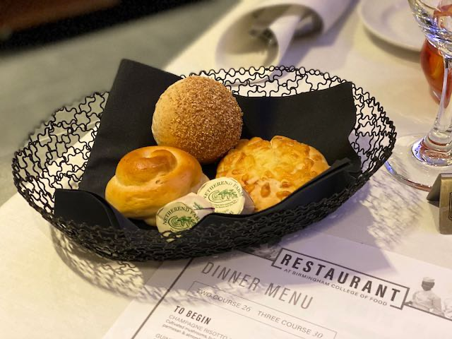 Three small bread rolls in a basket with butter pats