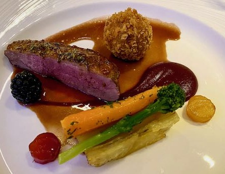 Pink duck breast with blackberry, candied beetroot circles, a duck croquette, pommes anna potatoes and veg, with a red cassis sauce and gravy