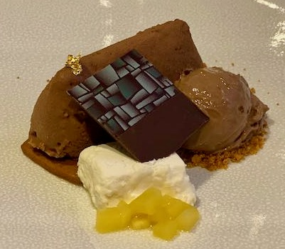 Toblerone box shaped chocolate mousse with a square of fancy chocolate, a scoop of chocolate ice cream, mango pieces, and passion fruit marsh mallow