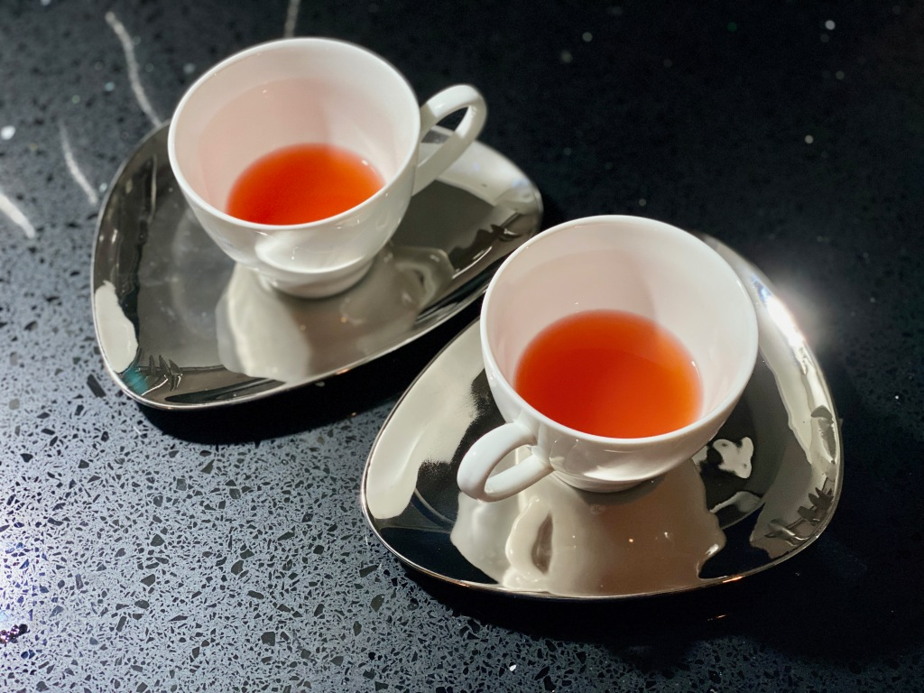 White tea cups filled with strawberry coloured clear liquid on silver teardrop saucers