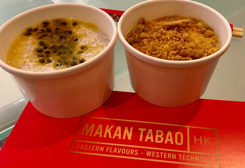 Two small round takeaway containers one with white sago pudding topped with passion fruit the other lime cheesecake topped with ginger crumb. Pots on Makan Tabao gold logo on red.