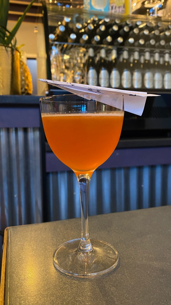 Pink cocktail with a paper aeroplane perched on the glass
